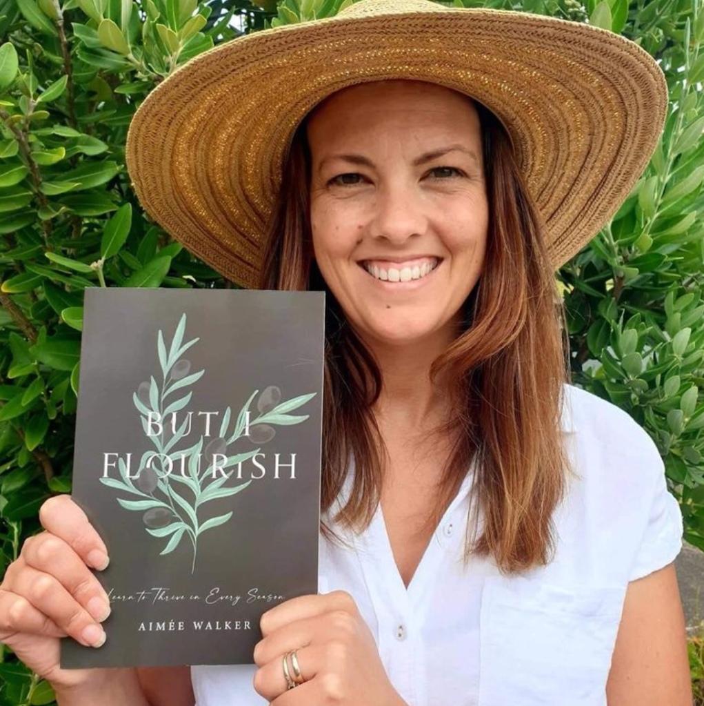 Aimée holds her first book But I Flourish